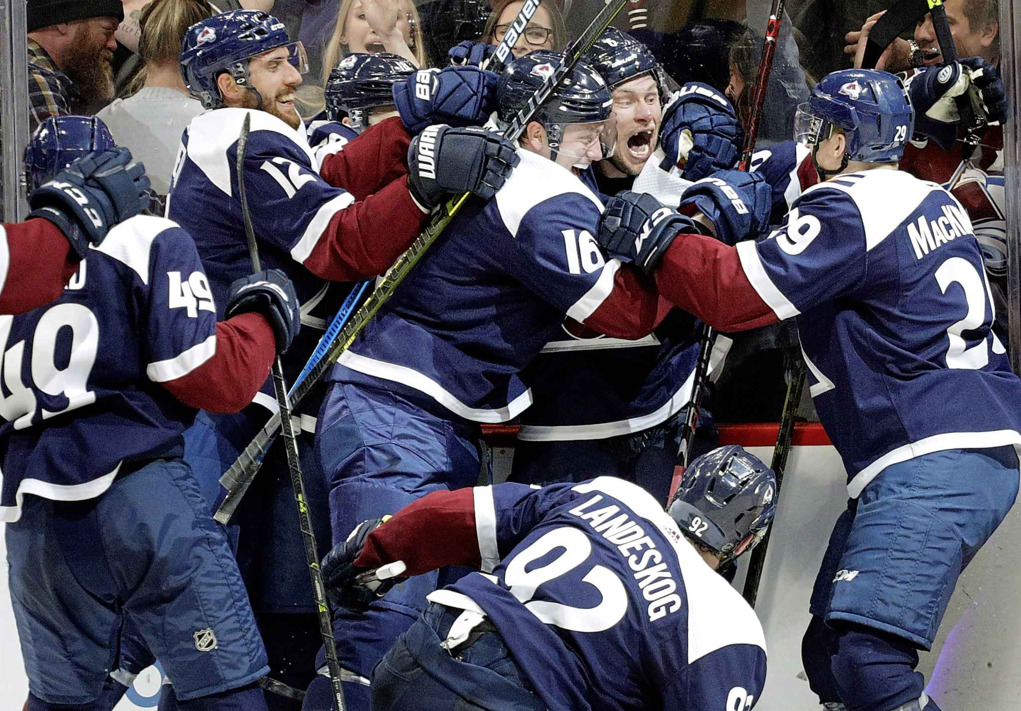 Colorado Avalanche defenceman Nikita Zadorov hugs defenceman Erik Johnson as centre Nathan MacKinnon joins the celebration after Johnson scored the game-winning goal in overtime against the Winnipeg Jets in Denver, Thursday.