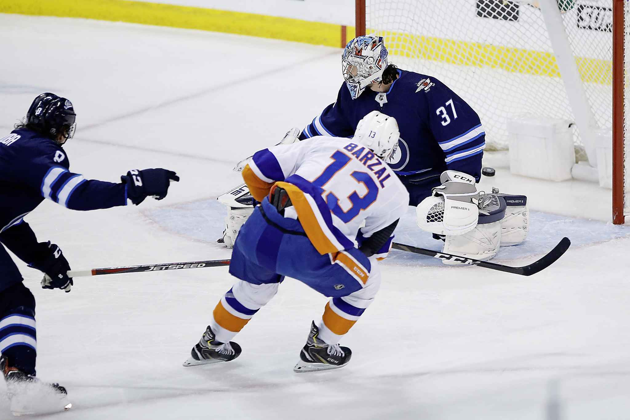 Winnipeg Jets goaltender Connor Hellebuyck can't stop a shot by New York Islanders' Mathew Barzal during the first period.