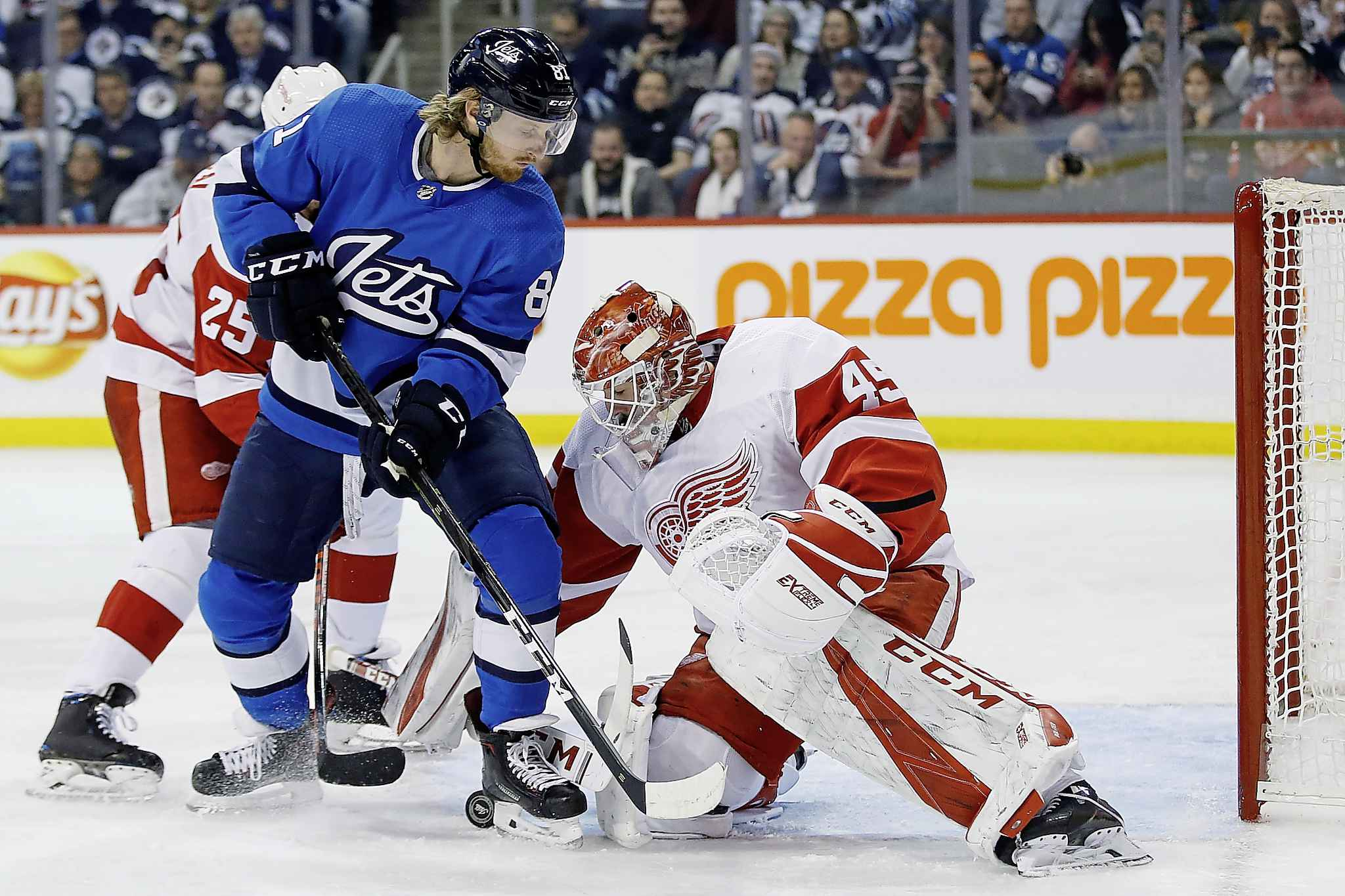 Detroit Red Wings goaltender Jonathan Bernier jumps on a loose puck as Winnipeg Jets' Kyle Connor applies pressure and Wings' Mike Green defends during the second period Friday.