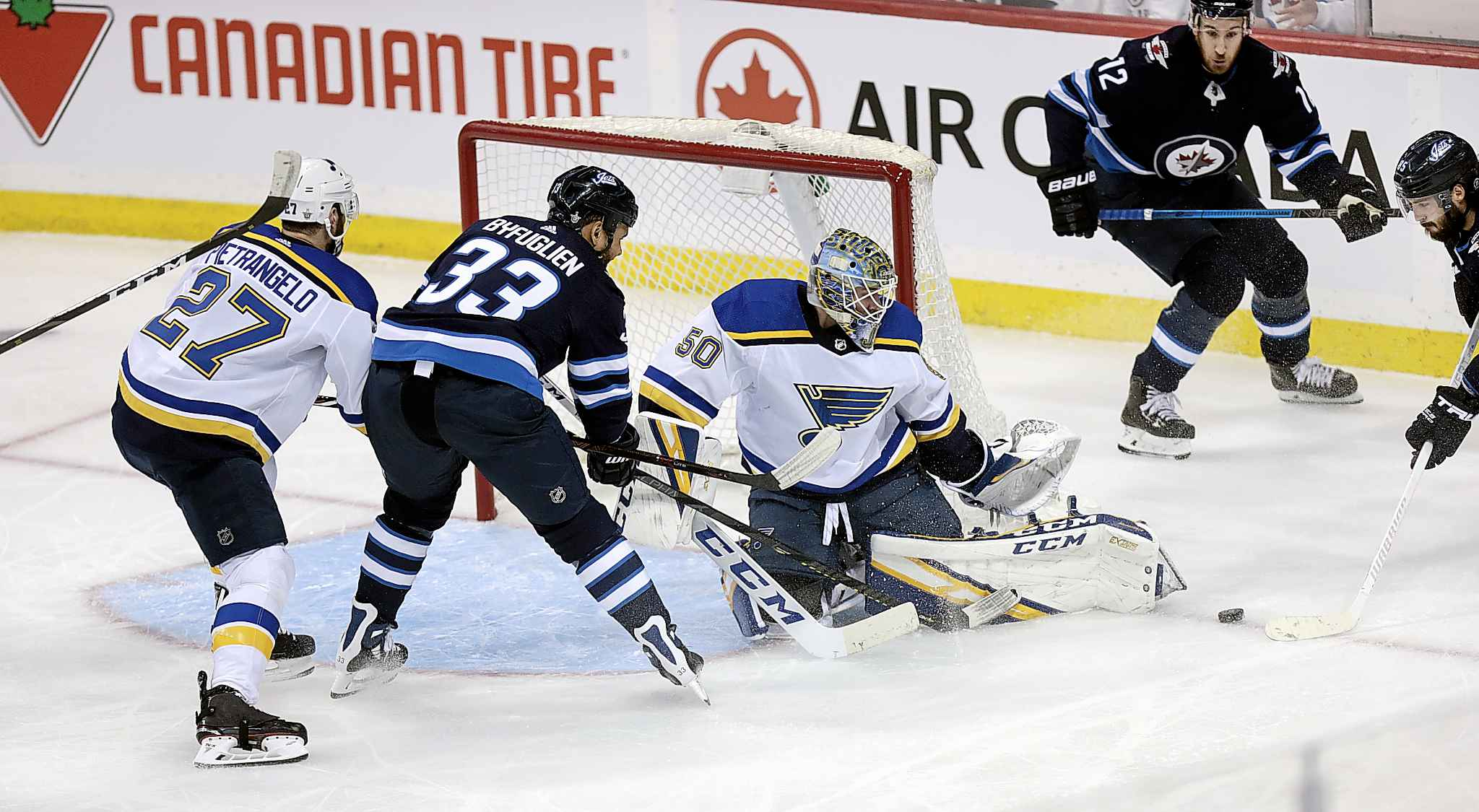 Winnipeg Jets' Dustin Byfuglien slams an attempt against the pads of Blues' netminder Jordan Binnington.