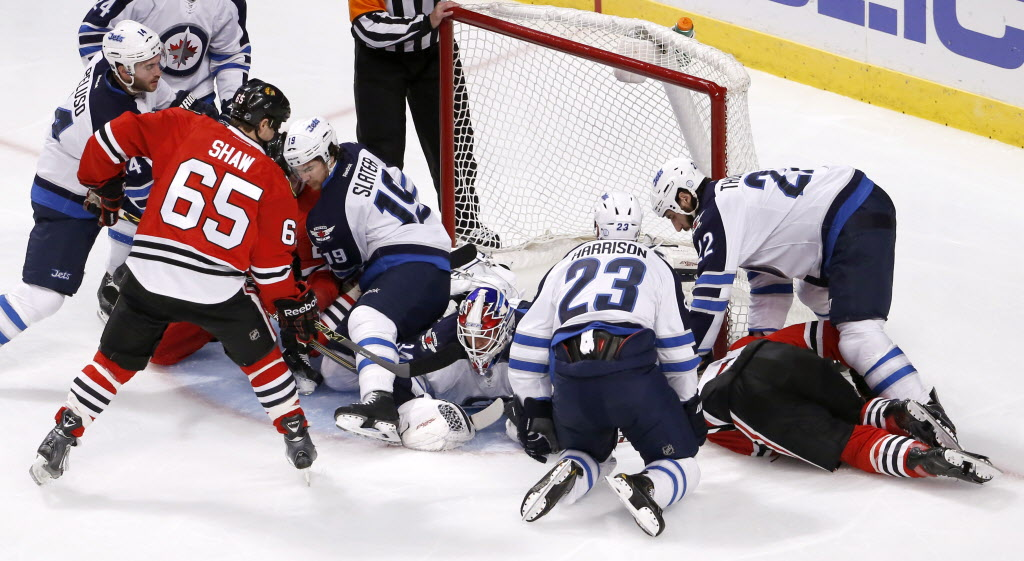 Winnipeg Jets goalie Michael Hutchinson makes a save during a pileup in front of the net. (Charles Rex Arbogast / The Associated Press )