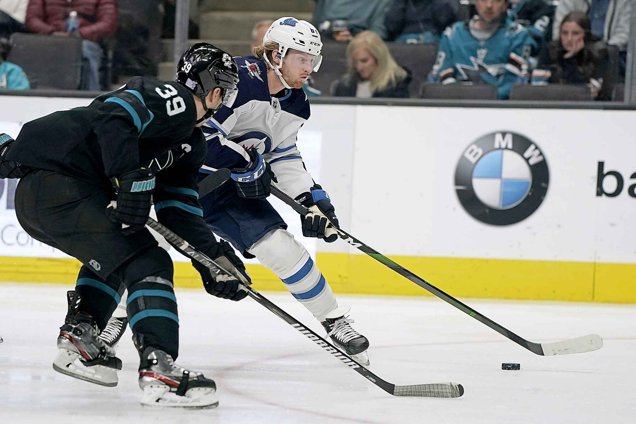 Winnipeg Jets left wing Kyle Connor works for the puck against San Jose Sharks centre Logan Couture during the second period.