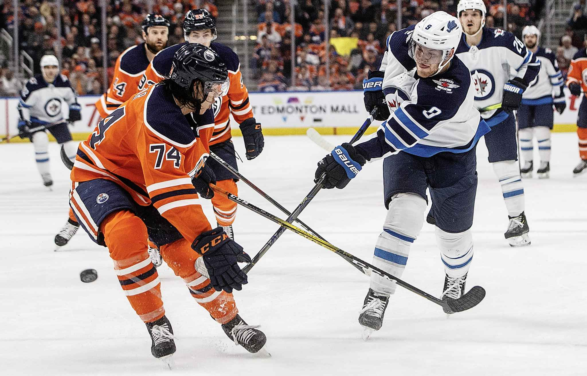Winnipeg Jets' Andrew Copp takes a shot as Edmonton Oilers' Ethan Bear  tries to block it during the first period in Edmonton on Wednesday.