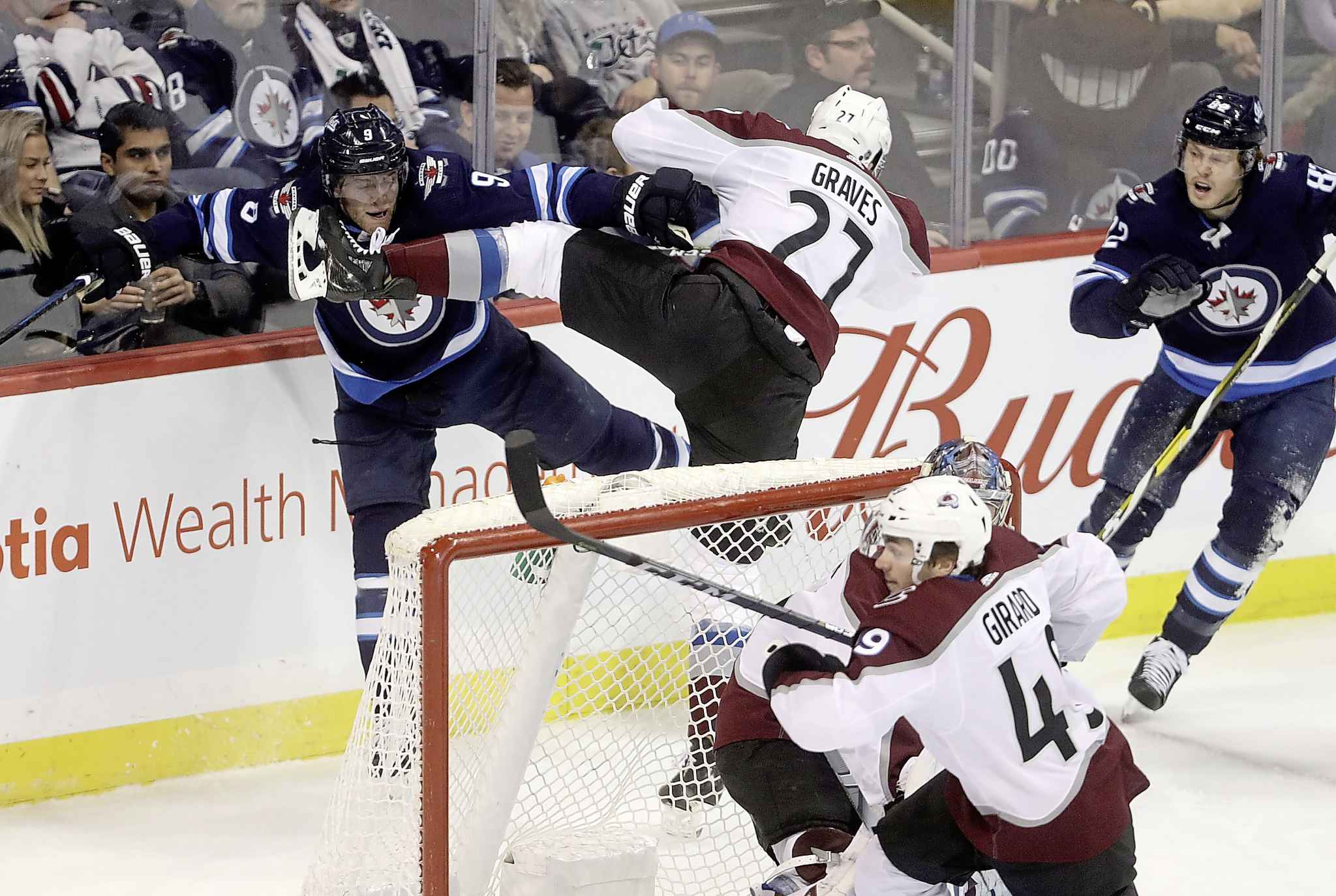 Winnipeg Jets' Andrew Copp gets a good look at the skate of Colorado Avalanche's Ryan Graves behind the net during some physical play in the first period Tuesday.
