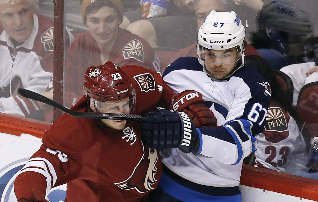 Phoenix Coyotes' Oliver Ekman-Larsson (23), of Sweden, gets hit in the face with a stick by Winnipeg Jets' Michael Frolik (67) during the second period. (Ross D. Franklin / The Associated Press )