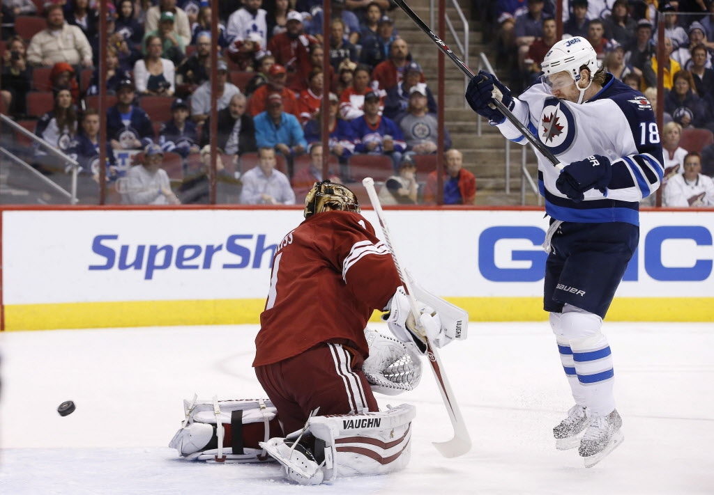 Winnipeg Jets' Bryan Little (18) tries to redirect the puck in front of Phoenix Coyotes' Thomas Greiss, left.