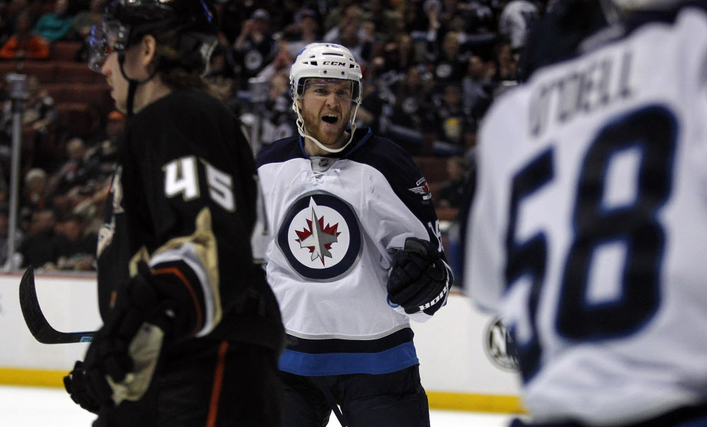 Winnipeg Jets' right wing Matt Halischuk, centre, reacts after scoring a first-period goal against Anaheim Ducks' defenseman Sami Vatanen (45), with Jets' centre Eric O'Dell (58) during Monday's game.