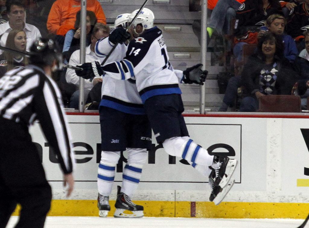 Winnipeg Jets' right wing Anthony Peluso (14) leaps in celebration into left wing Eric Tangradi, left, after Tangradi scores in the second period of Monday's game against the Anaheim Ducks. (Alex Gallardo / The Associated Press)
