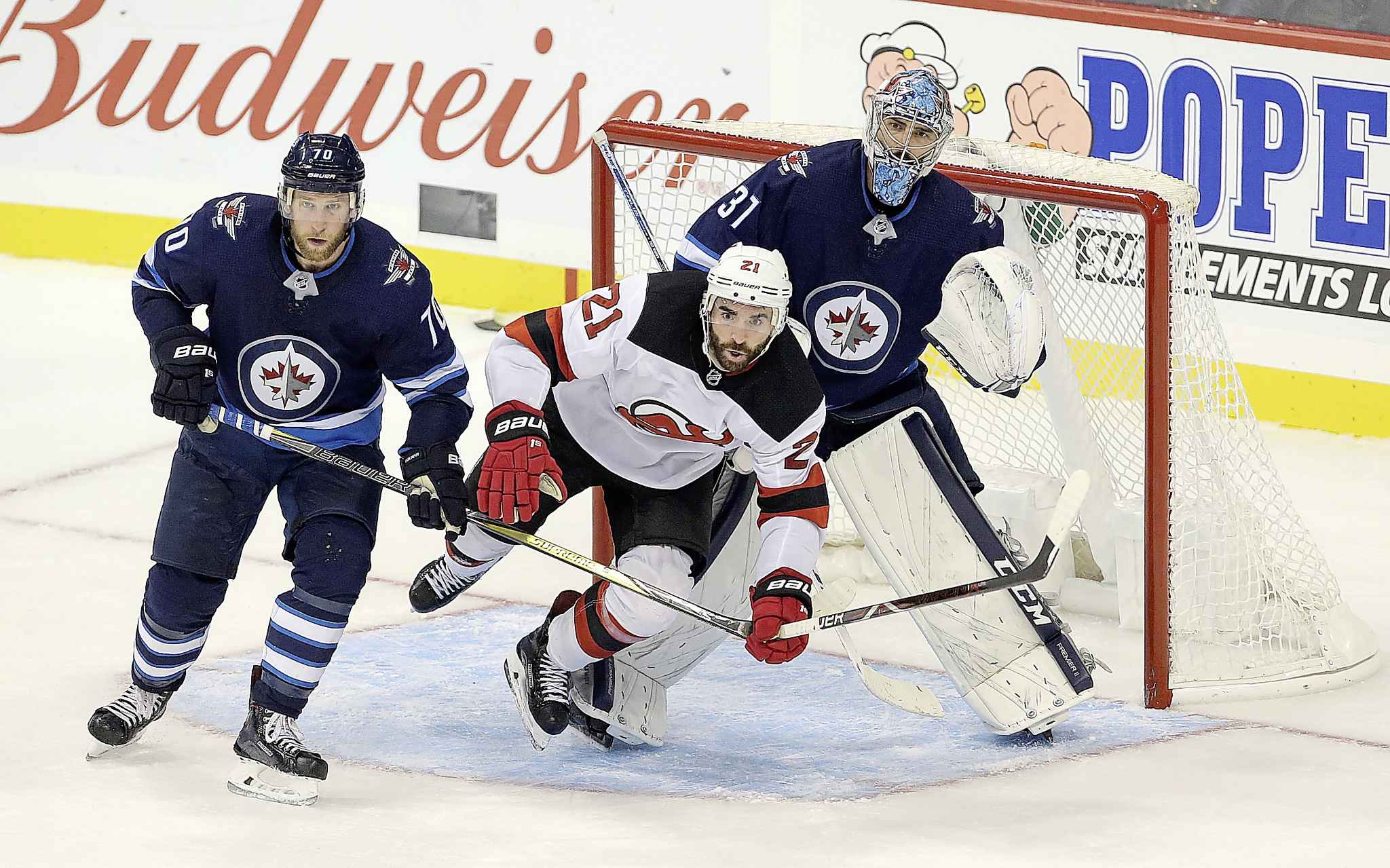 New Jersey Devils forward Kyle Palmieri ights for space in front of Winnipeg Jets goaltender Connor Hellebuyck and defenceman Joe Morrow during the third period.