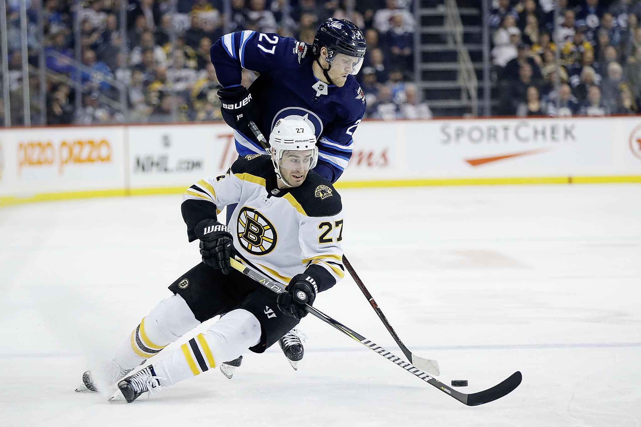 Winnipeg Jets' Nikolaj Ehlers changes direction on Boston Bruins' John Moore as he breaks for the net during the second period.