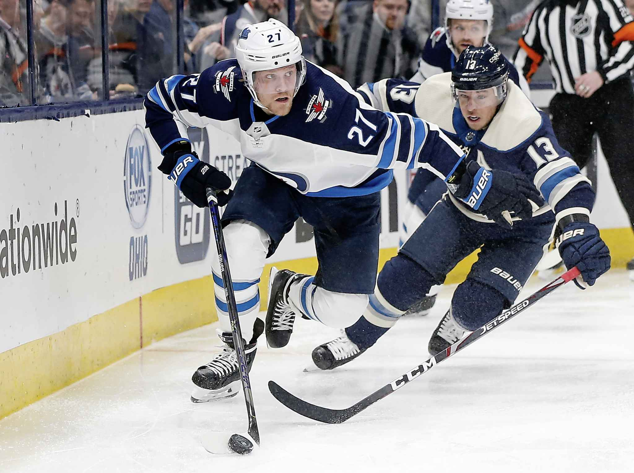 Winnipeg Jets' Nikolaj Ehlers tries to clear the puck as Columbus Blue Jackets' Cam Atkinson chases him behind the net during the second period.