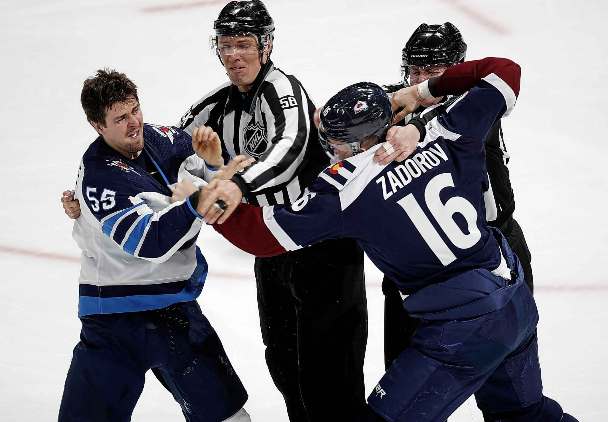 Winnipeg Jets centre Mark Scheifele, left, is restrained by the linesmen as Colorado Avalanche defenceman Nikita Zadorov squares off to fight in the third period.
