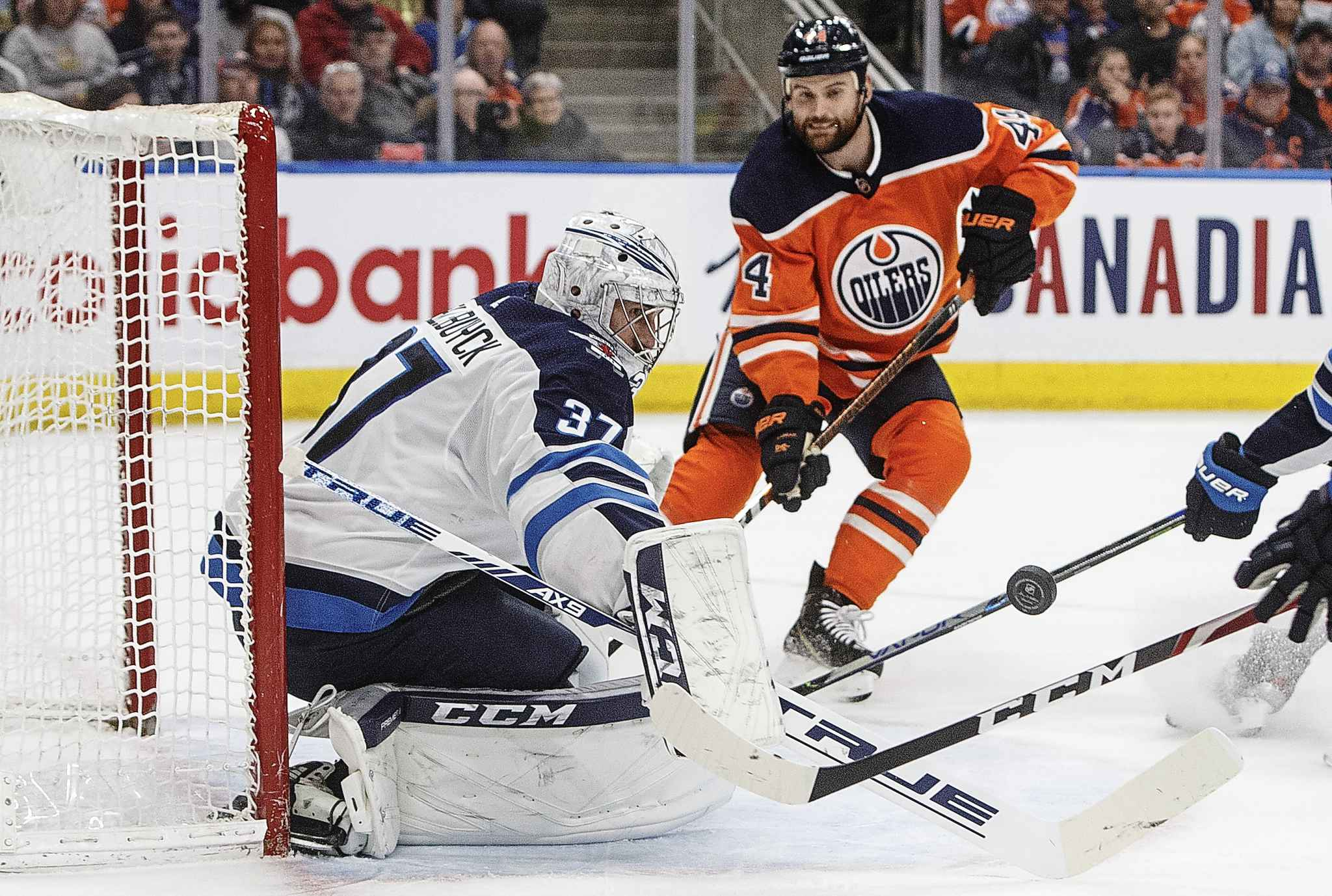 Jets goalie Connor Hellebuyck makes a save as Edmonton Oilers' Zack Kassian looks for the rebound during the second period.
