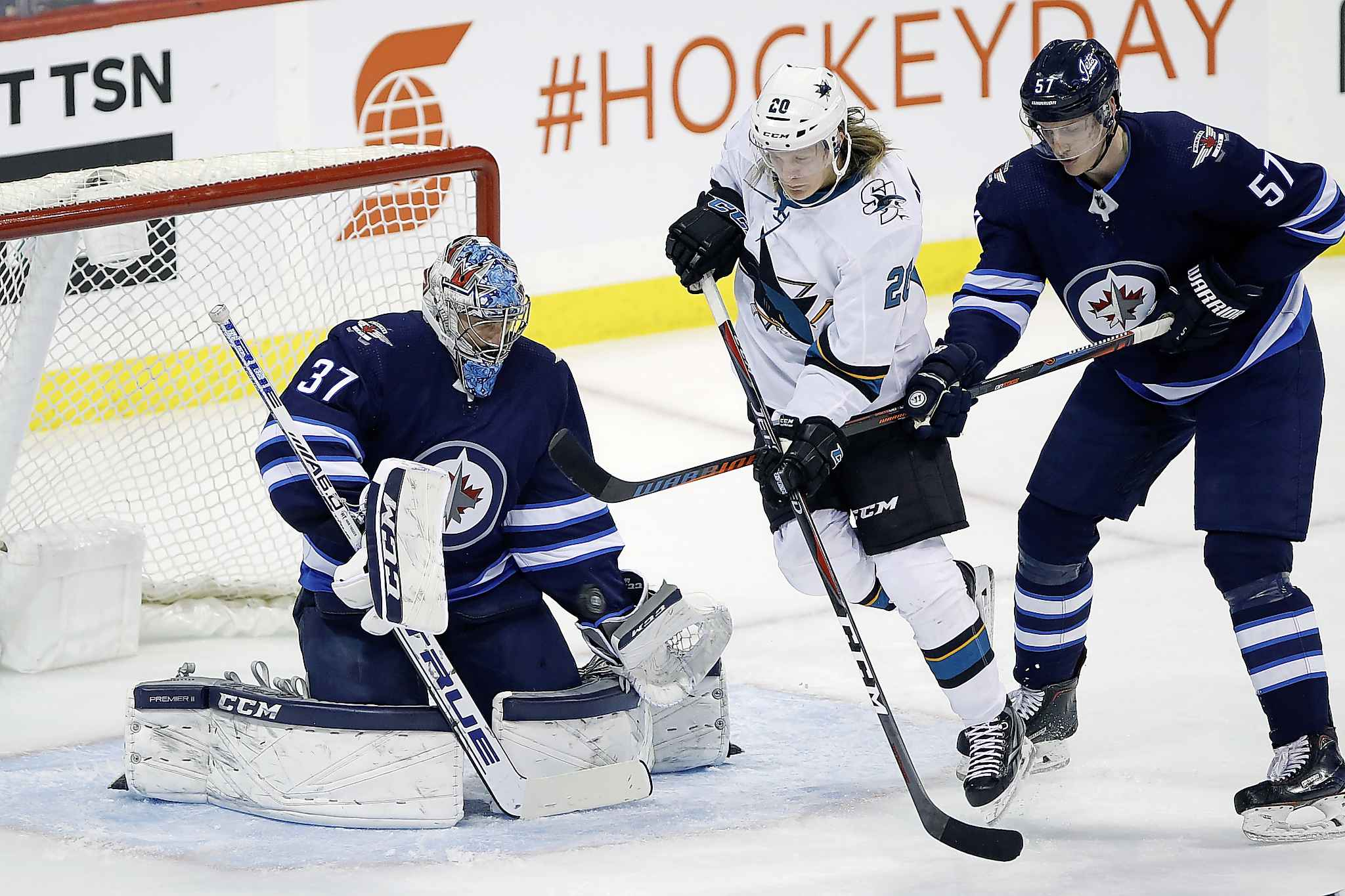 San Jose Sharks' Marcus Sorensen attempts to deflect the puck past Winnipeg Jets goaltender Connor Hellebuyck as Tyler Myers defends during the first period.