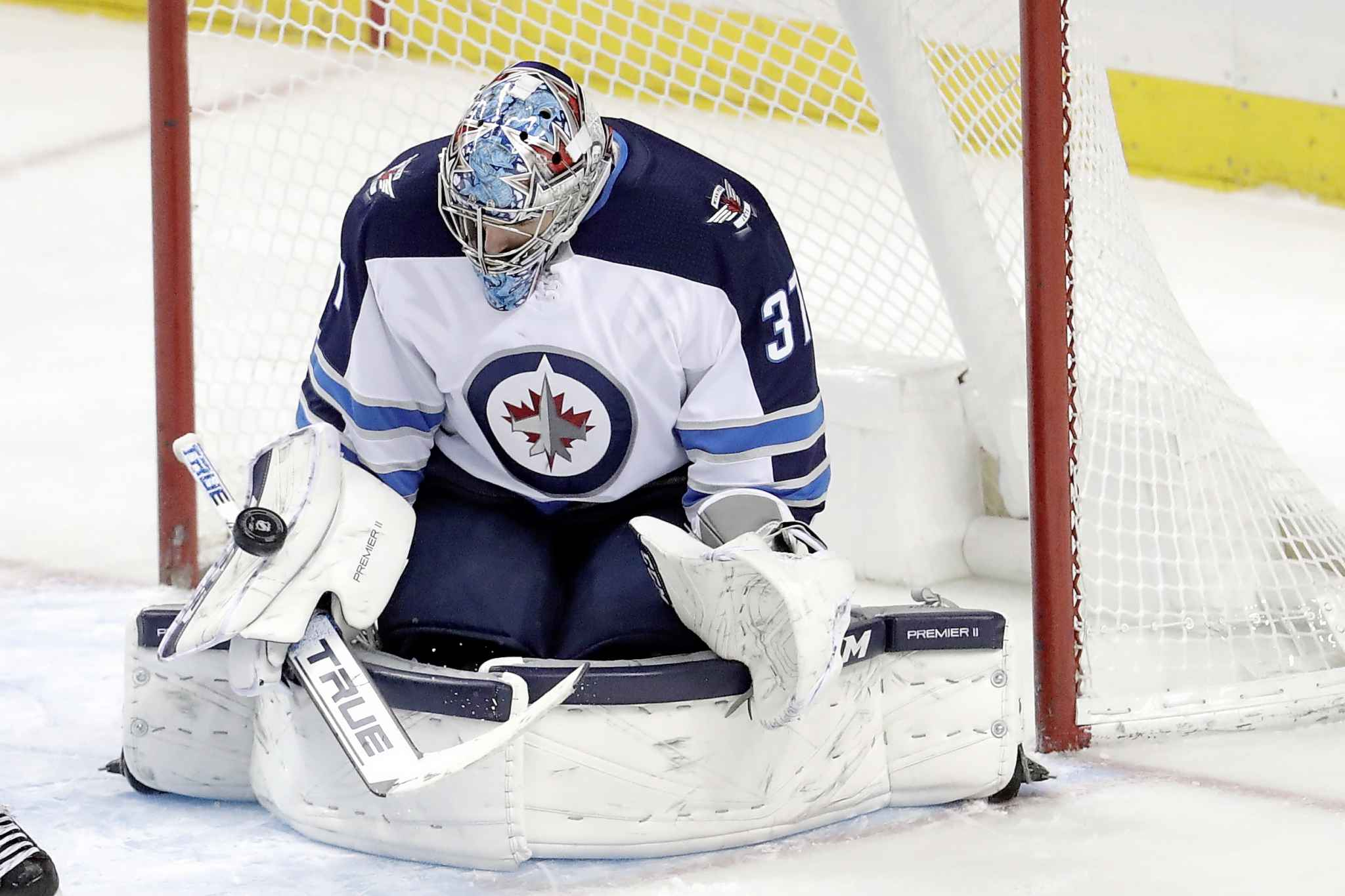 Winnipeg Jets goaltender Connor Hellebuyck stops a shot by the New York Islanders during the third period.