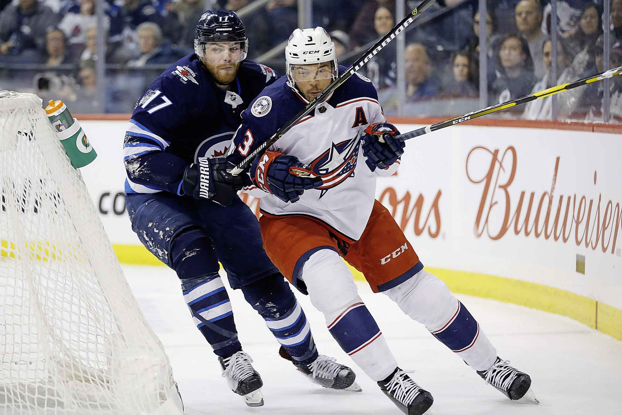 Winnipeg Jets' Adam Lowry chases Columbus Blue Jackets' Seth Jones around the net during the second period Thursday.
