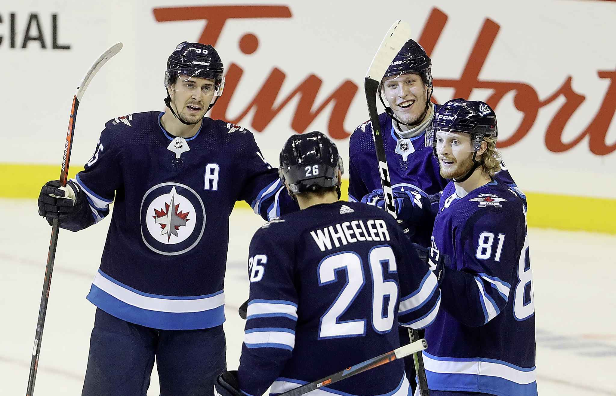 Winnipeg Jets' Mark Scheifele, Blake Wheeler, Patrik Laine and Kyle Connor celebrate after Laine scored a power-play goal late in the first period.