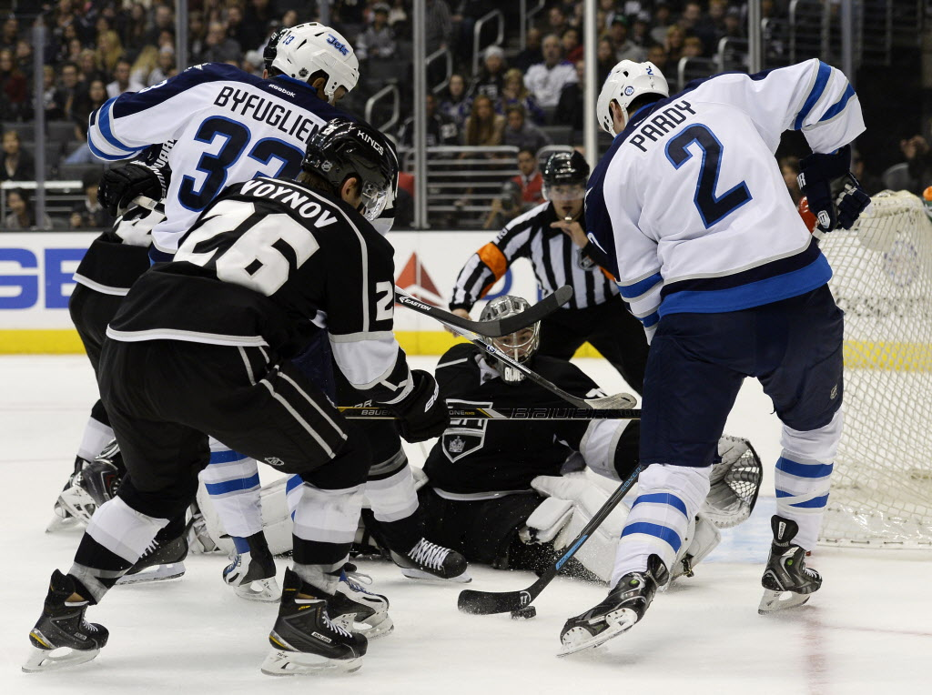 Los Angeles Kings goalie Jonathan Quick blocks a shoot on goal by Winnipeg Jets defenseman Adam Pardy, right, during the first period of the game Saturday in Los Angeles.  (Kevork Djansezian / The Associated Press )
