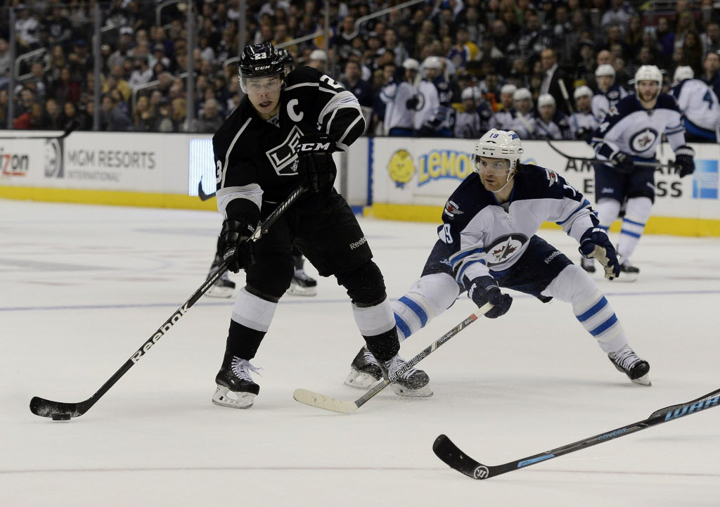 Los Angeles Kings right wing Dustin Brown (23) looks to pass the puck as he pressured by Winnipeg Jets center Jim Slater (19) during the second period of an NHL hockey game at the Staples Center.