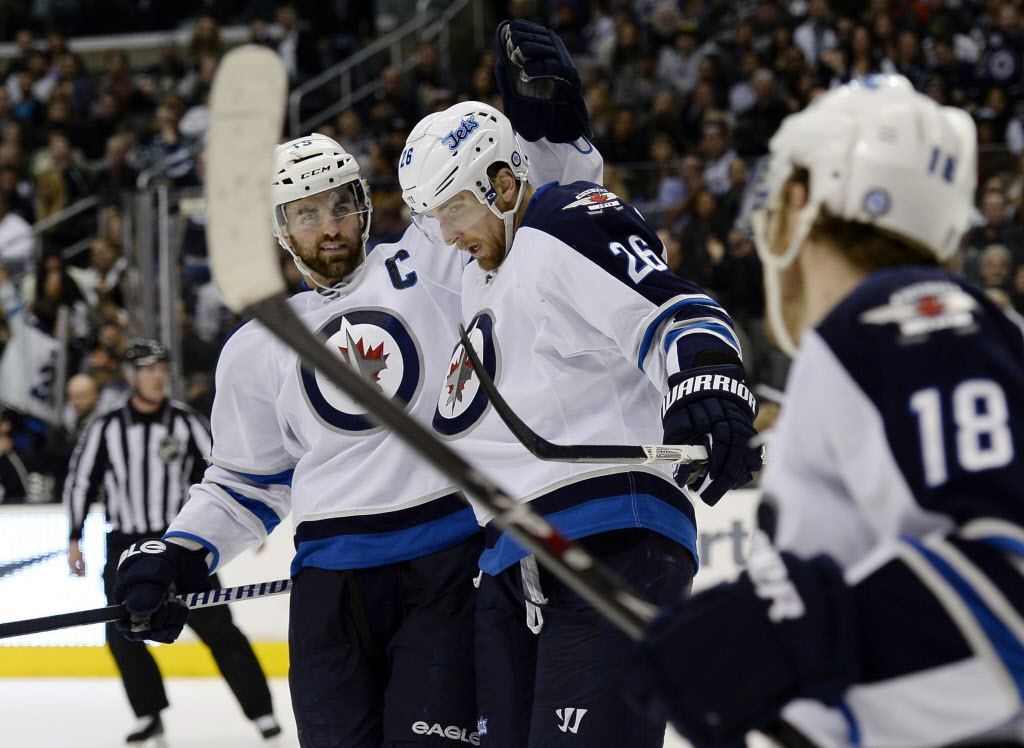 Winnipeg Jets right wing Blake Wheeler (26) celebrates his goal with left wing Andrew Ladd (16) ancenter Bryan Little (18) against Los Angeles Kings goalie Jonathan Quick during the third period.