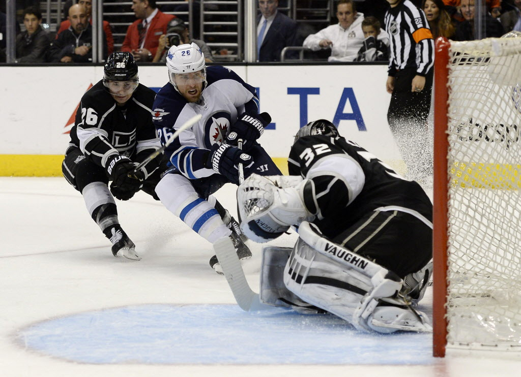 Winnipeg Jets right wing Blake Wheeler (26) scores a goal against Los Angeles Kings goalie Jonathan Quick (32) as Kings' Slava Voynov (26) defends during the third period.