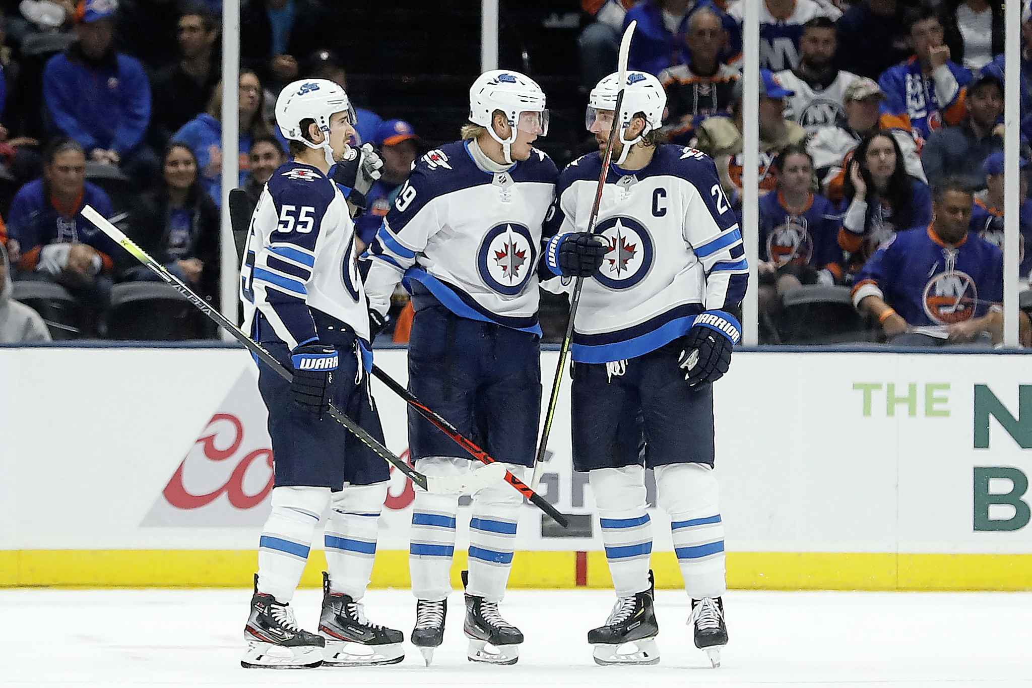 Winnipeg Jets right wing Patrik Laine, middle, celebrates with center Mark Scheifele (55) and right wing Blake Wheeler after scoring a goal against the New York Islanders during the second period of an NHL hockey game Sunday, Oct. 6, 2019, in Uniondale, N.Y. (AP Photo/Michael Owens)