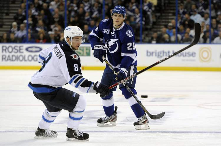 Tampa Bay Lightning defenceman Matt Carle passes the puck past Winnipeg Jets centre Alexander Burmistrov during an NHL game in Tampa, Fla., Thursday.