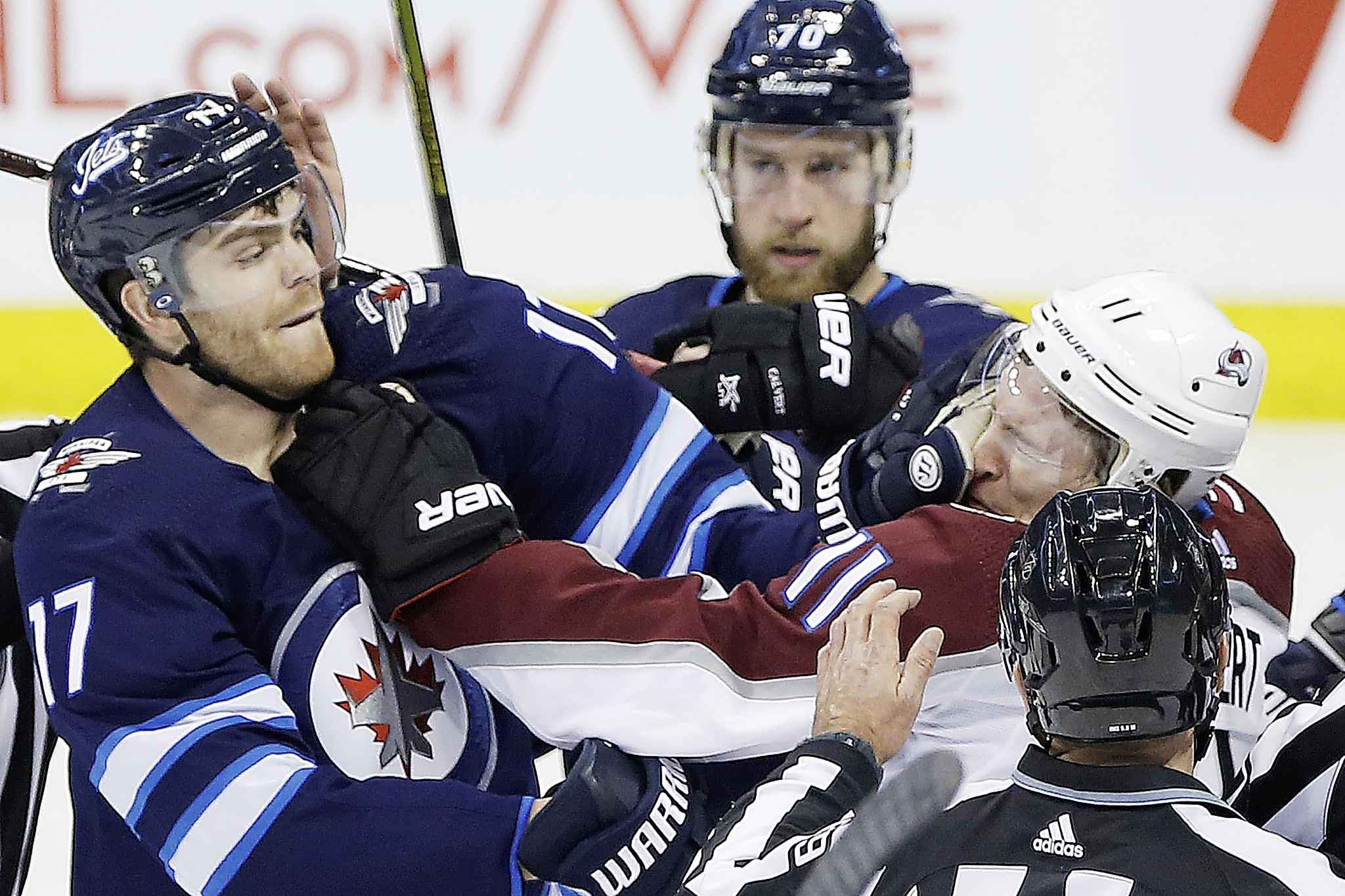 Winnipeg Jets' Adam Lowry lands one to the face of Colorado Avalanche's Matt Calvert as Jets' Joe Morrow  looks on during the second period.