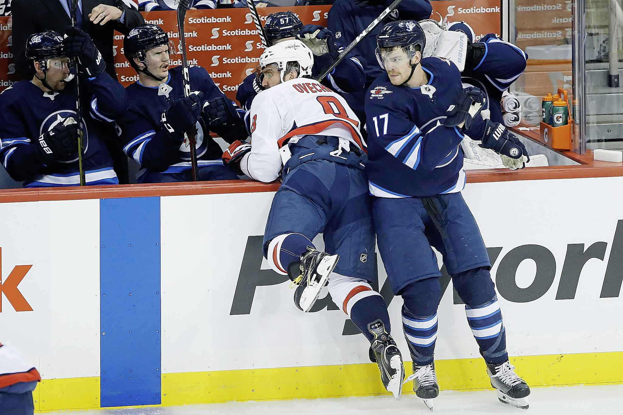 Winnipeg Jets' Adam Lowry checks Washington Capitals' Alex Ovechkin during the first period.