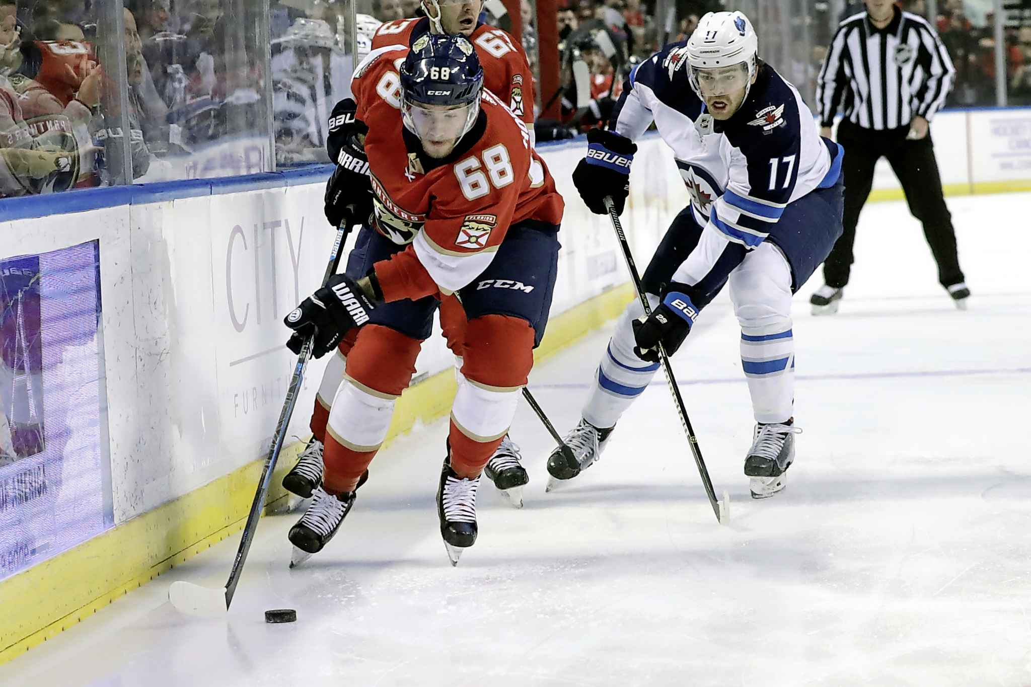 Florida Panthers centre Mike Hoffman skates with the puck with Winnipeg Jets' Adam Lowry in pursuit during the first period.