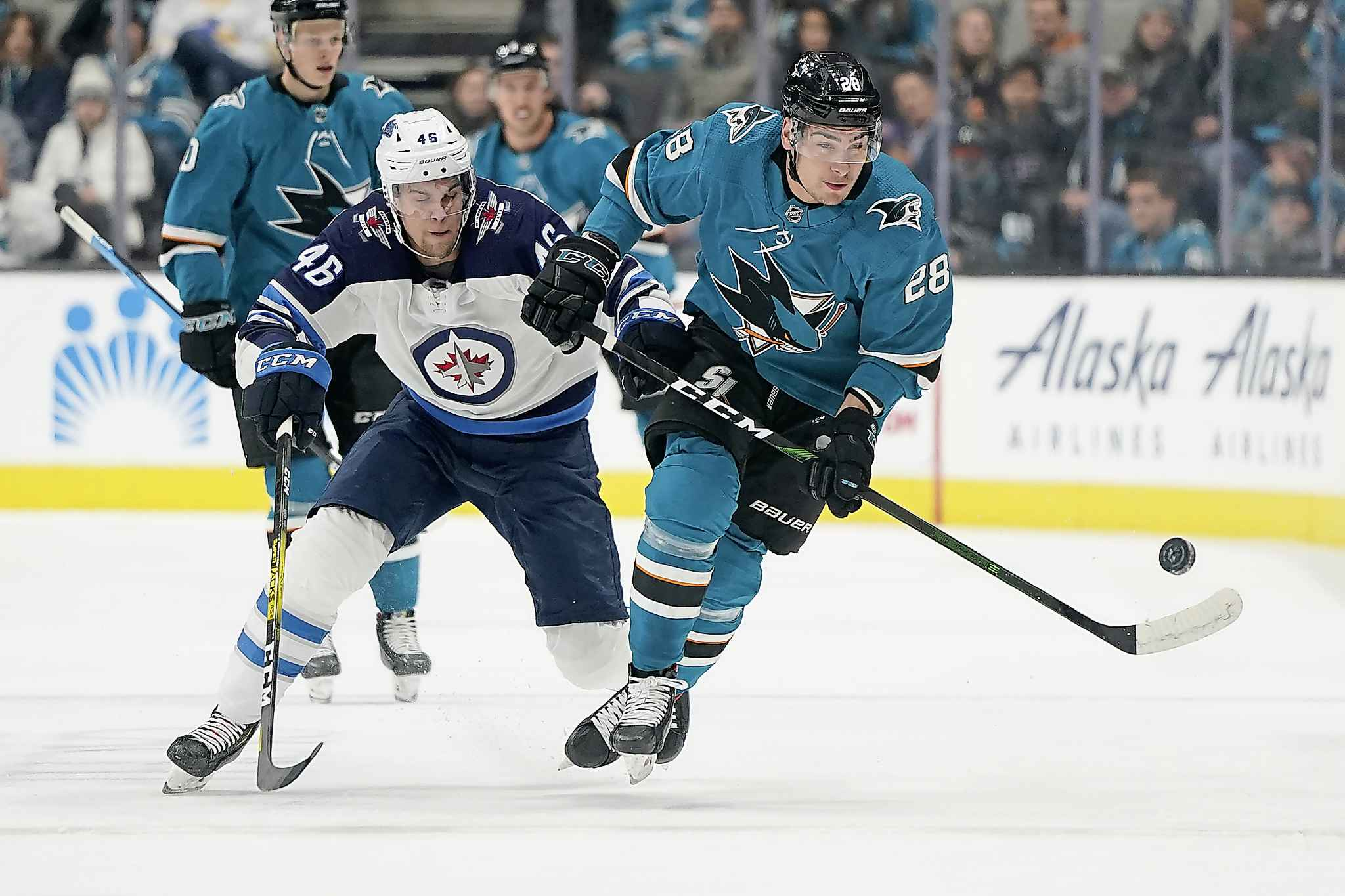 San Jose Sharks right wing Timo Meier competes for the puck with Winnipeg Jets left wing Joona Luoto  during the first period.