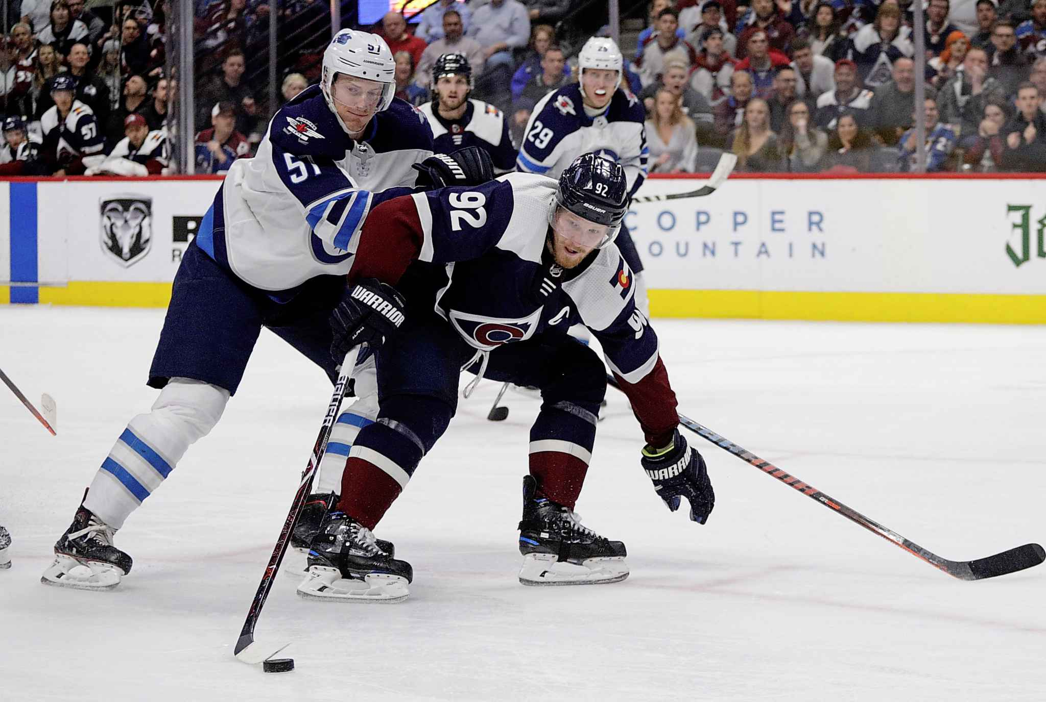 Colorado Avalanche left wing Gabriel Landeskog (92) carries the puck past Winnipeg Jets defenseman Tyler Myers (57) during the second period of an NHL hockey game in Denver, Thursday, April 4, 2019. (AP Photo/Joe Mahoney)