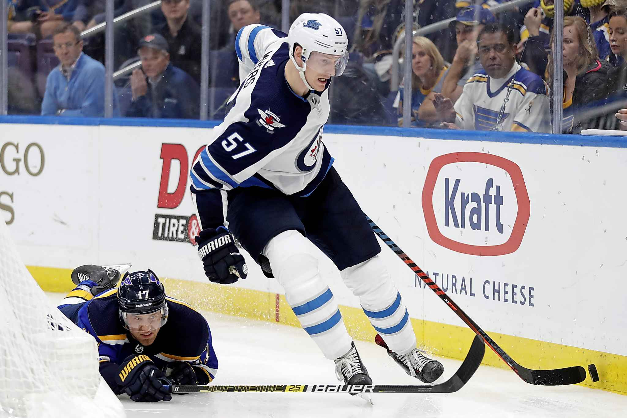 Winnipeg Jets defenseman Tyler Myers (57) moves the puck past the reach of St. Louis Blues left wing Jaden Schwartz (17) during overtime in Game 4 of an NHL hockey first-round playoff series Tuesday, April 16, 2019, in St. Louis. (AP Photo/Jeff Roberson)