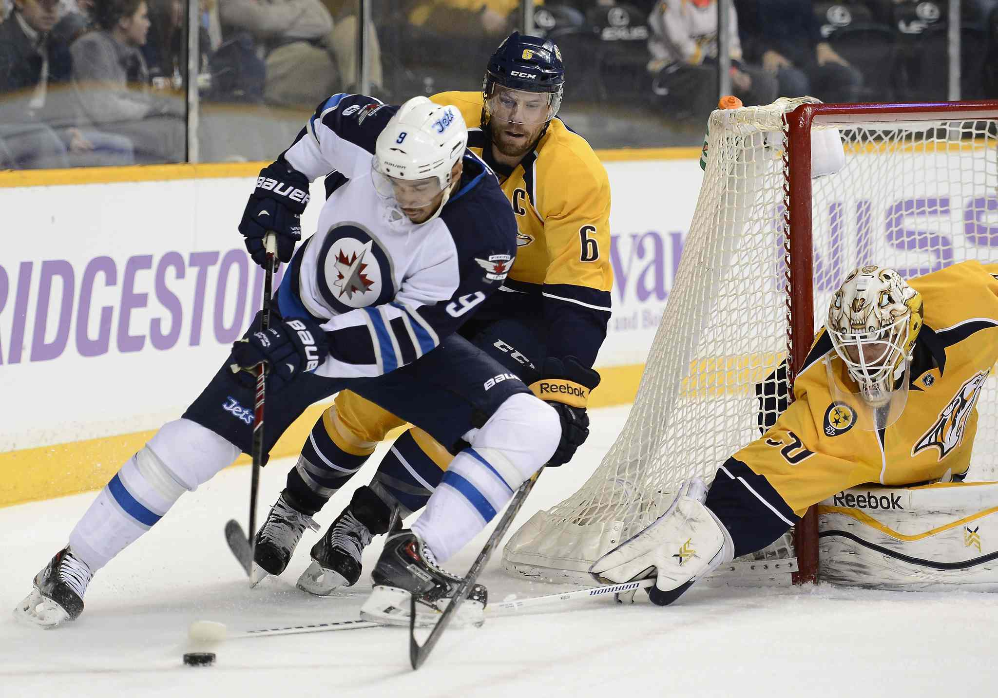 Evander Kane brings the puck around the net as he is shadowed by Nashville Predators defenceman Shea Weber in Nashville.