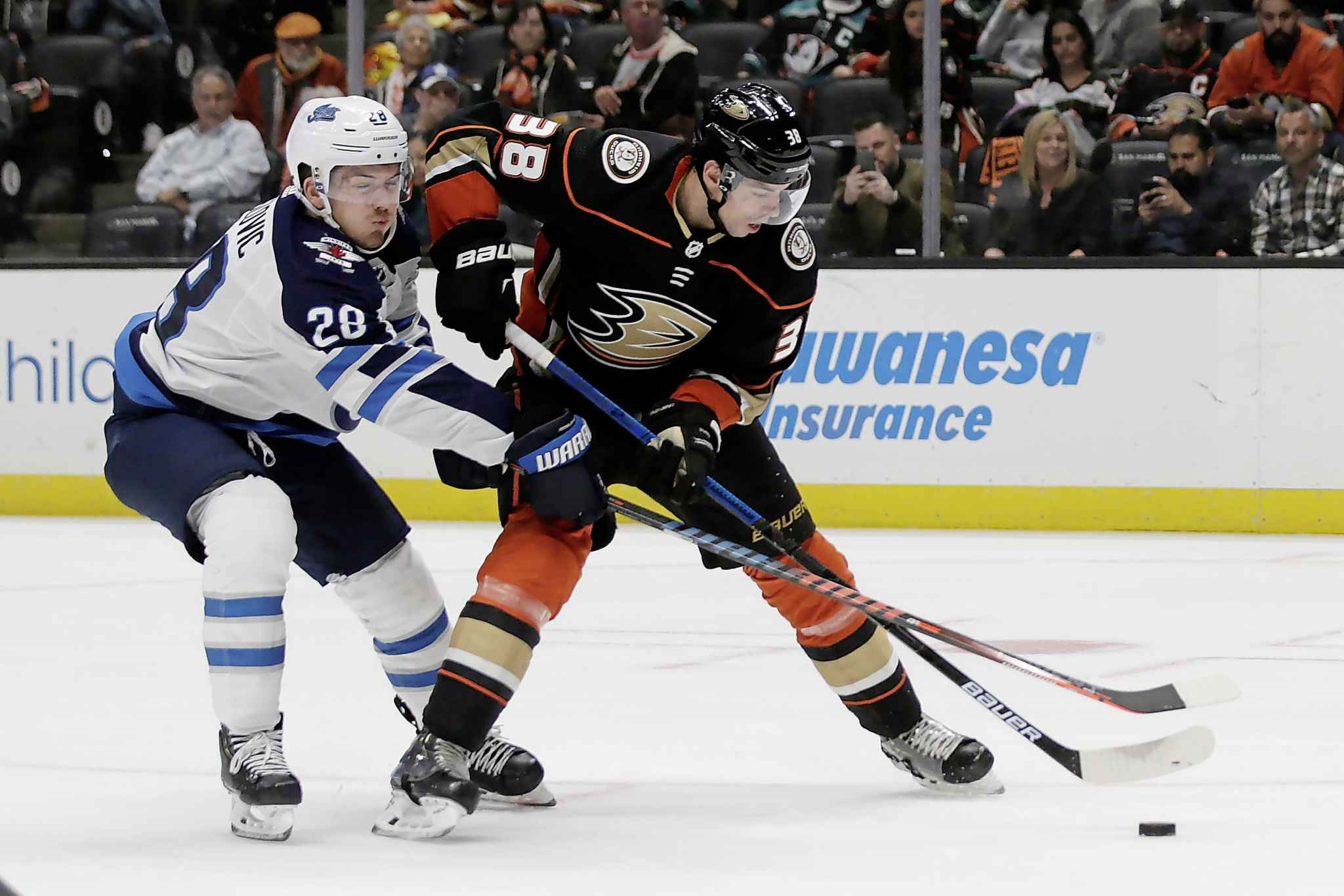 Anaheim Ducks centre Derek Grant, right, controls the puck in front of Winnipeg Jets' Jack Roslovic during the second period.