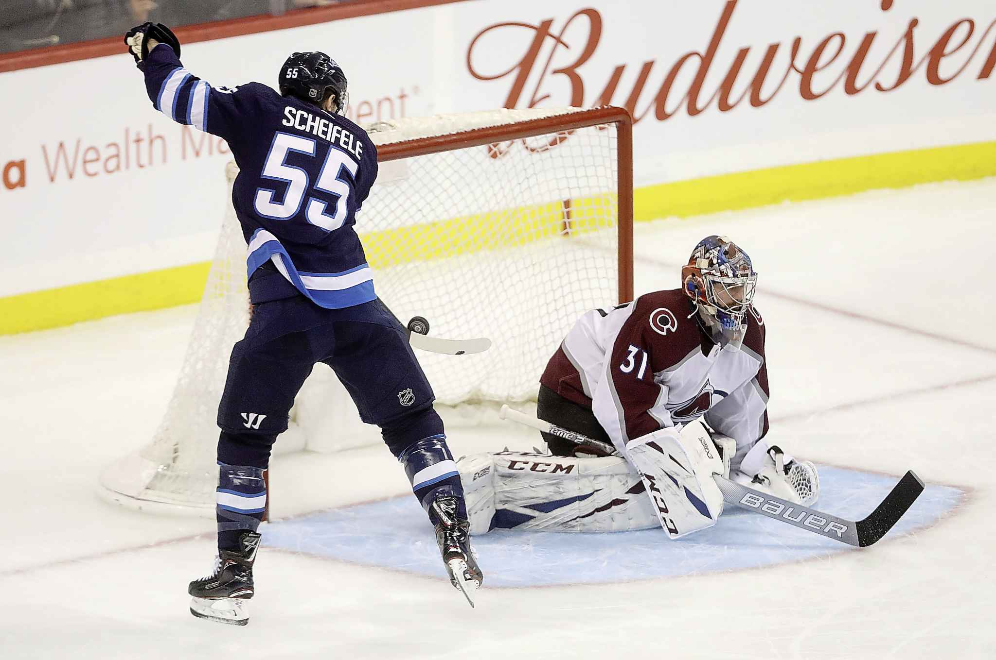 Winnipeg Jets' Mark Scheifele knocks his own rebound out of the air and into the back of the net behind Colorado Avalanche goaltender Philipp Grubauer during the third period Tuesday.