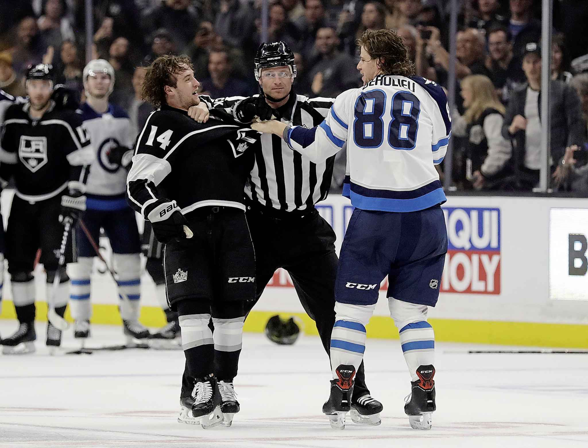 Los Angeles Kings' Brendan Leipsic, left, and Winnipeg Jets' Nathan Beaulieu are separated by an official during the second period Monday, in Los Angeles.