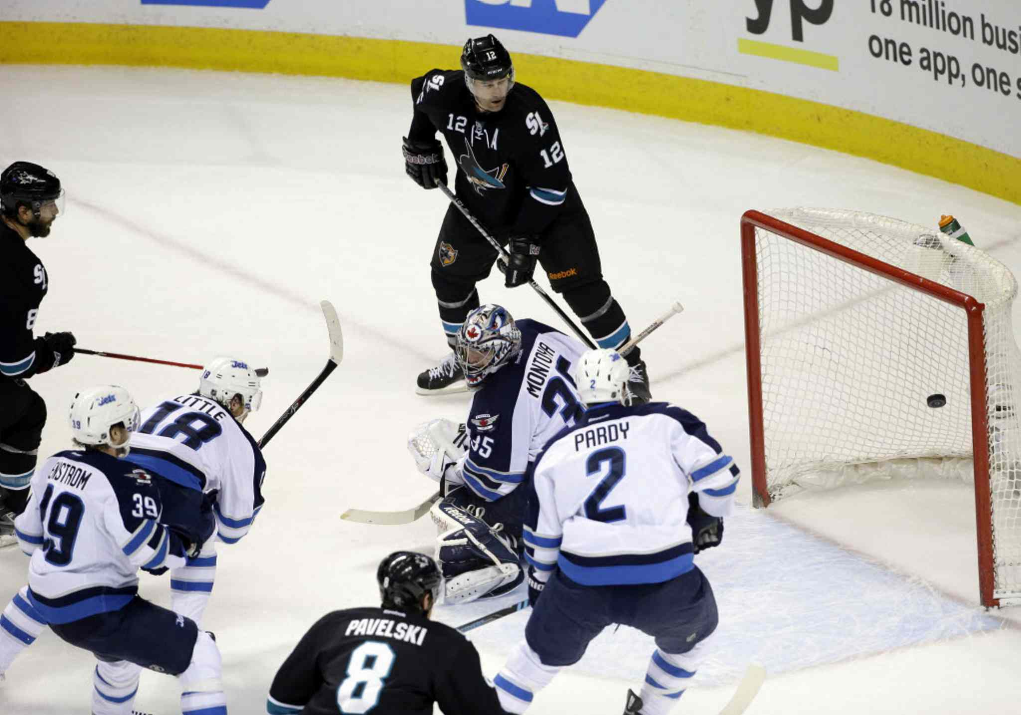 San Jose Sharks' Brent Burns, left, scores past Winnipeg Jets goalie Al Montoya, center, during the first period.