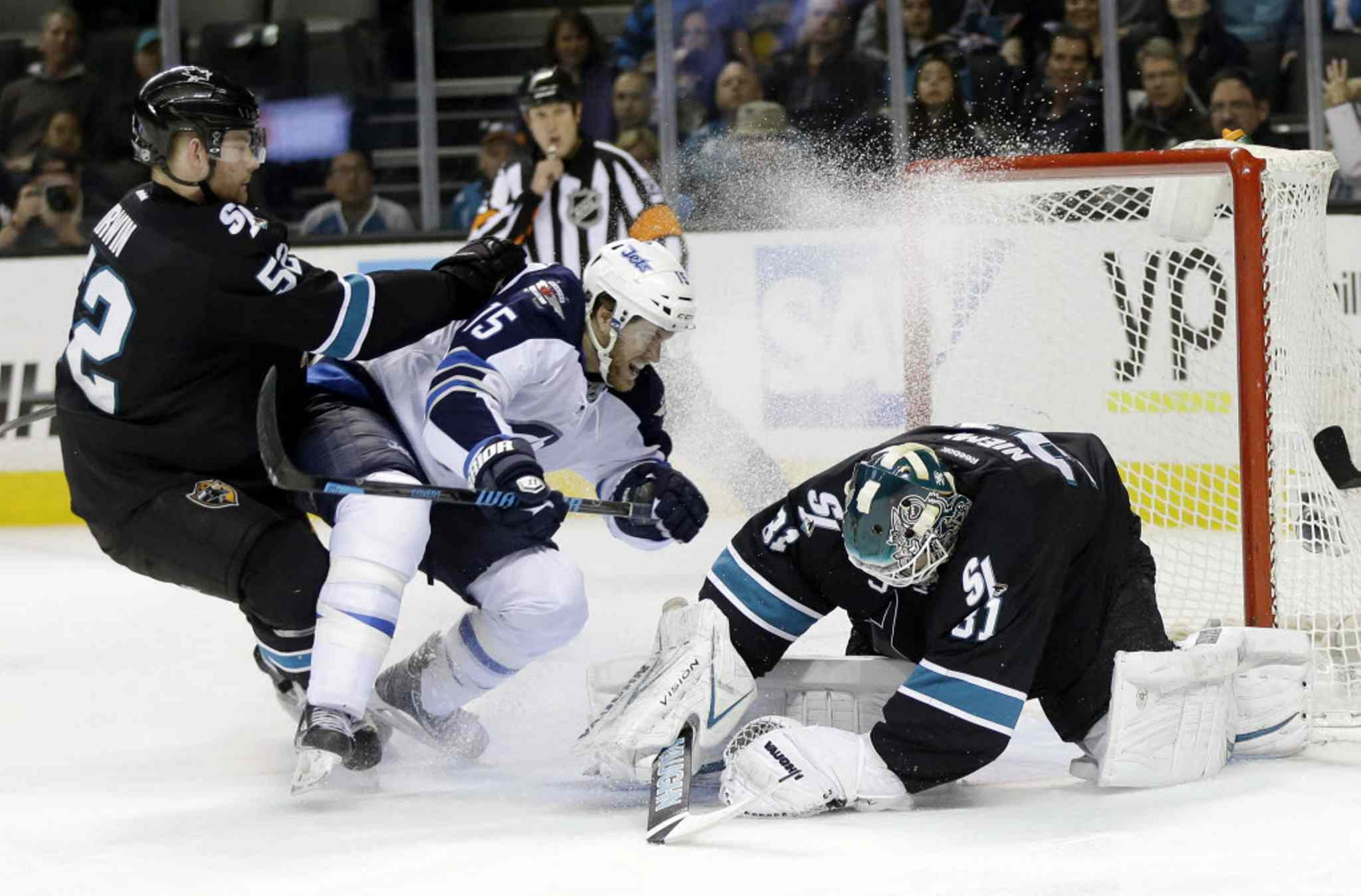 San Jose Sharks goalie Antti Niemi, right, stops a shot next to Winnipeg Jets' Matt Halischuk (15) and teammate Matt Irwin (52) during the second period on Thursday.