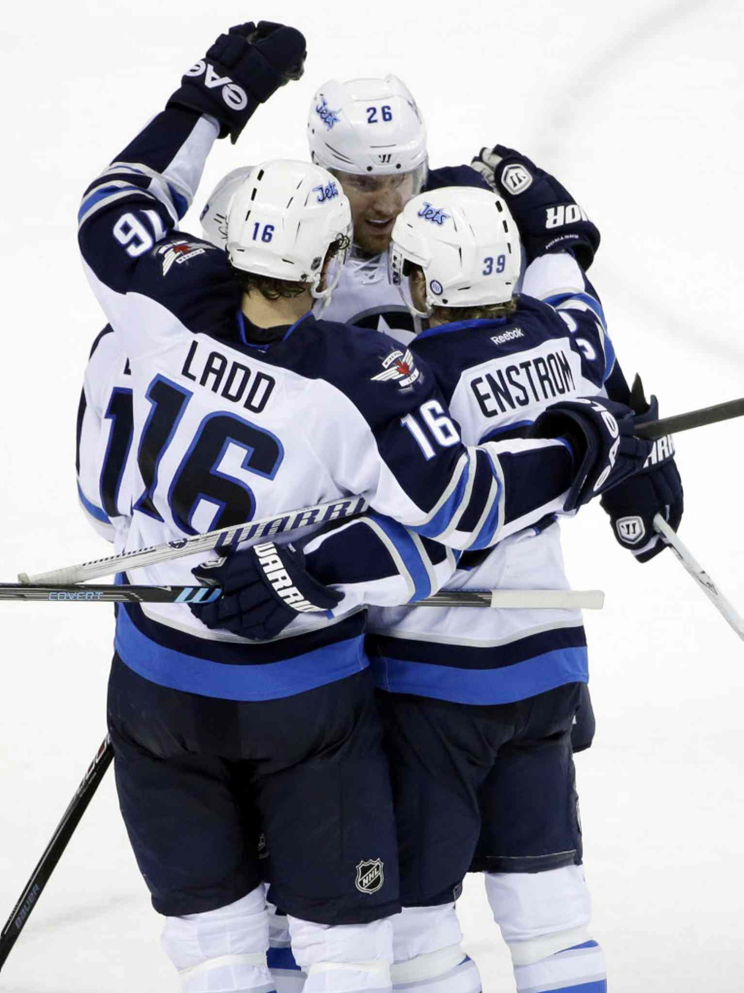 Winnipeg Jets' Tobias Enstrom is hugged by teammates after scoring the go-ahead goal against the San Jose Sharks during the third period.