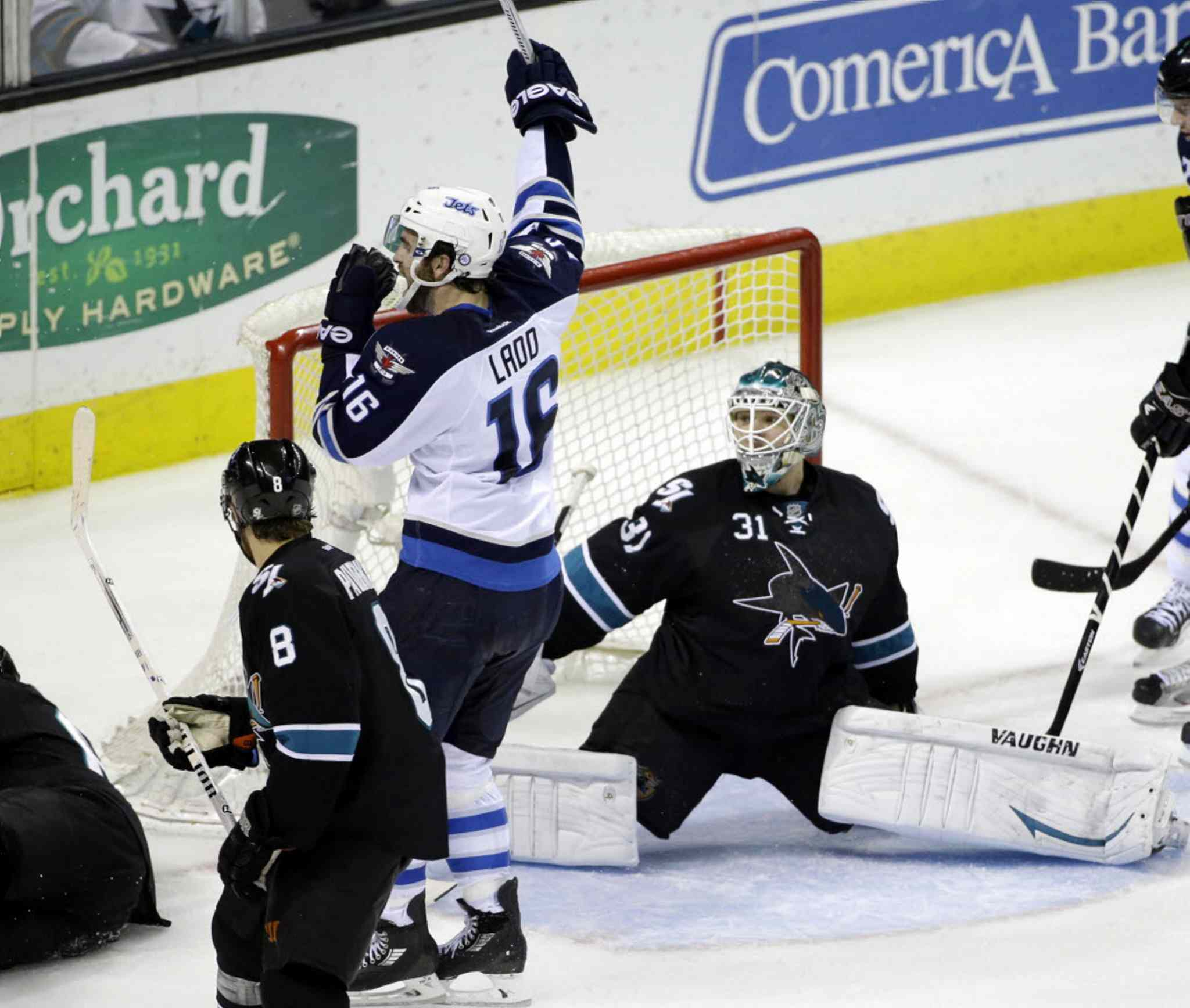 Winnipeg Jets' Andrew Ladd (16) celebrates a goal by teammate Tobias Enstrom, next to San Jose Sharks goalie Antti Niemi (31), during the third period.