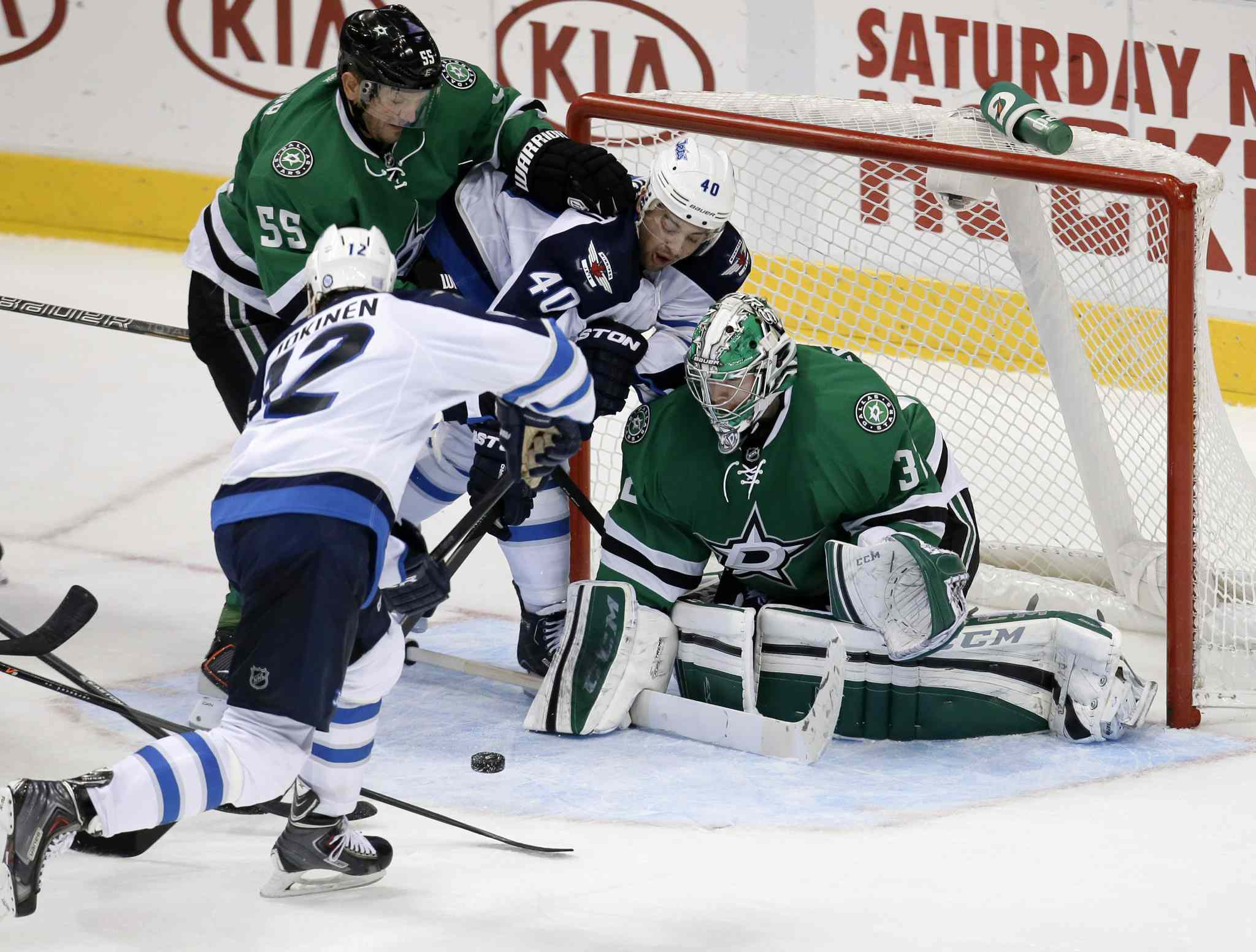 Olli Jokinen attempts a shot on a rebound against Dallas Stars goalie Kari Lehtonen as defenceman Sergei Gonchar grapples with Devin Setoguchi in front of the net during overtime.