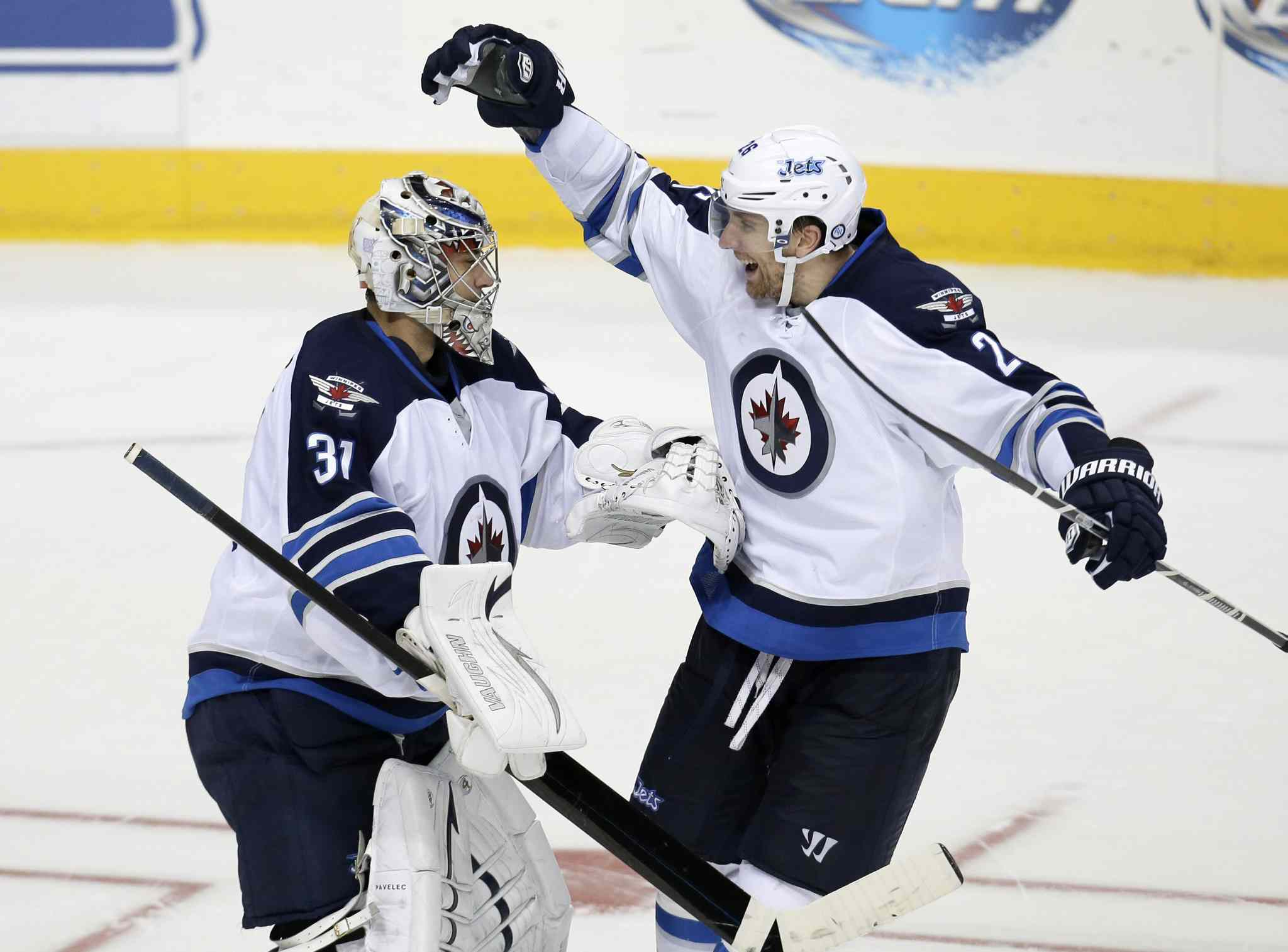 Ondrej Pavelec celebrates with Blake Wheeler after a shootout.