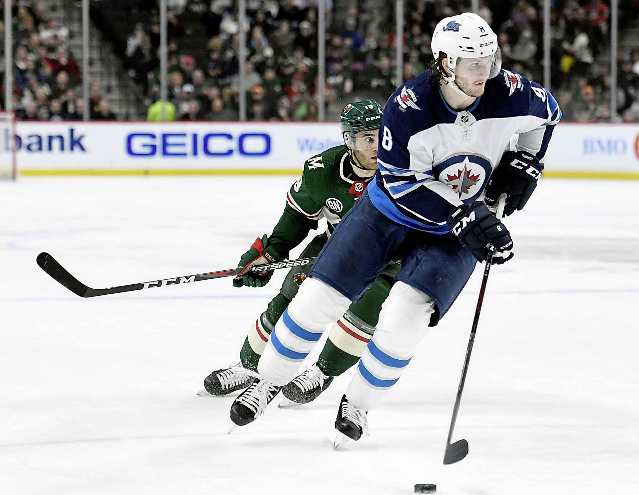 Winnipeg Jets defenceman Jacob Trouba carries the puck while shorthanded against Minnesota Wild centre Luke Kunin during the second period Tuesday. Trouba would score on the play.