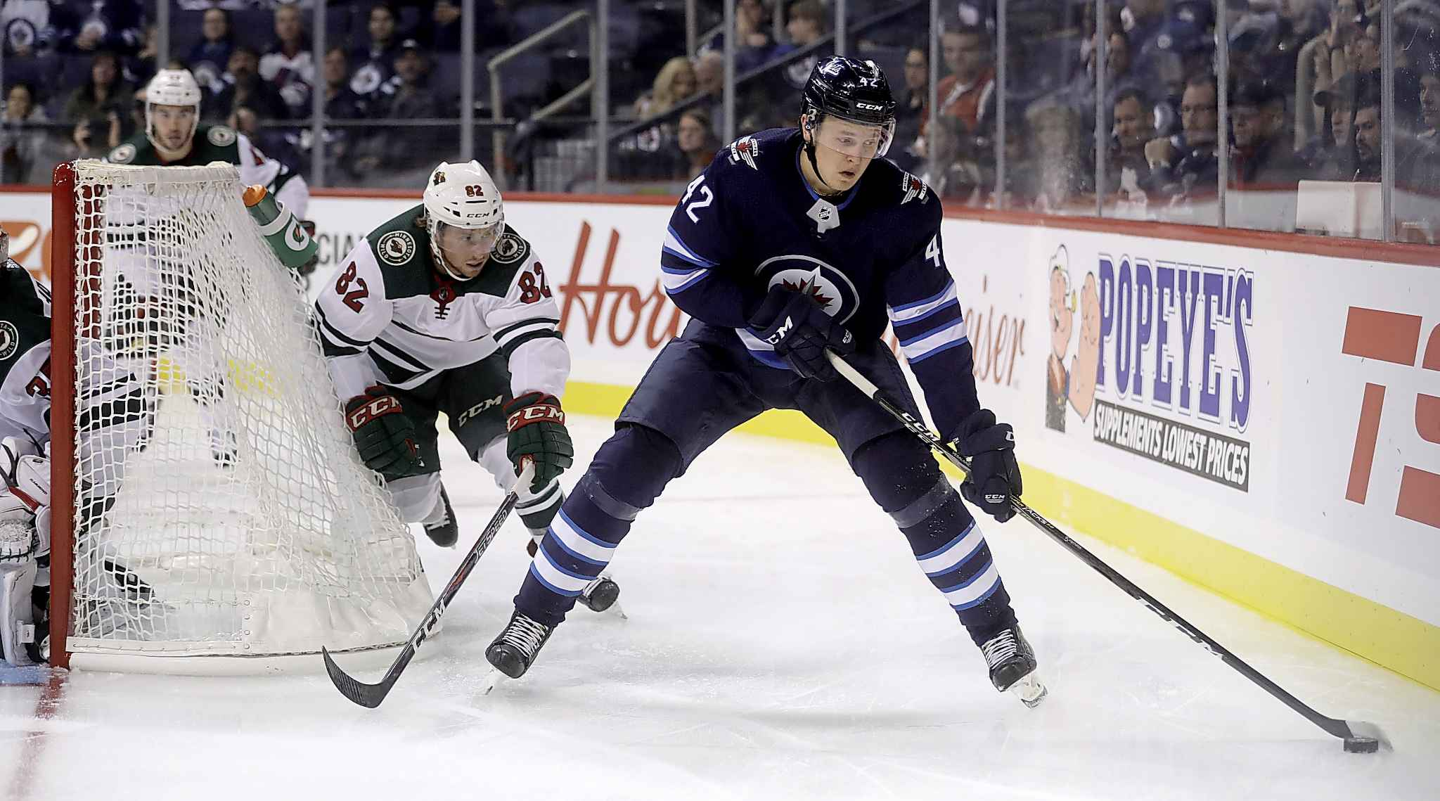 Winnipeg Jets' Kristian Vesalainen carries the puck in front of Minnesota Wild's Justin Kloos behind the Minnesota goal during second period preseason NHL hockey in Winnipeg, Monday. Along with line mates Mathieu Perreault and Jack Roslovic, Vesalainen had some of the more entertaining shifts of the game for the Jets.