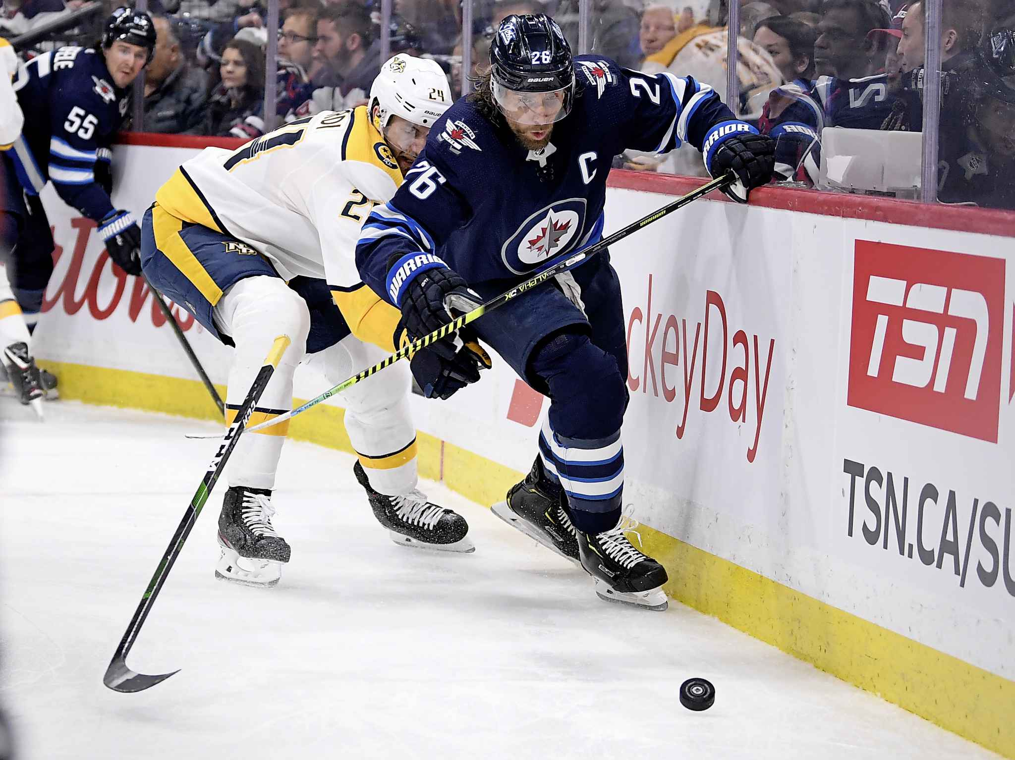Winnipeg Jets' Blake Wheeler and Nashville Predators' Jarred Tinordi skate after a loose puck during the second period.