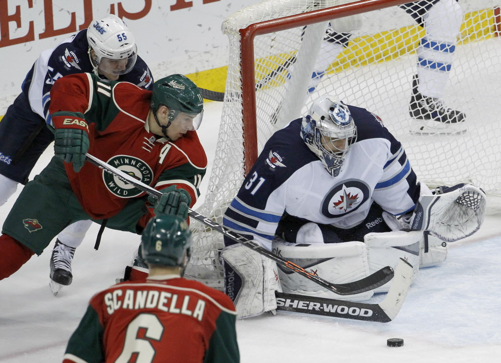 Minnesota Wild left wing Zach Parise (11) reaches for the puck in front of Winnipeg Jets goalie Ondrej Pavelec (31) as  Jets centre Mark Scheifele, rear left, defends during the third period. The Jets won 2-0.