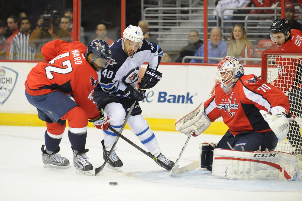 Winnipeg Jets' right wing Devin Setoguchi (40) tries get a first-period shot off with pressure form Washington Capitals' right wing Joel Ward (42), with Washington Capitals goalie Braden Holtby (70) in the goal on Thursday. (Mitchell Layton / Tribune Media MCT)