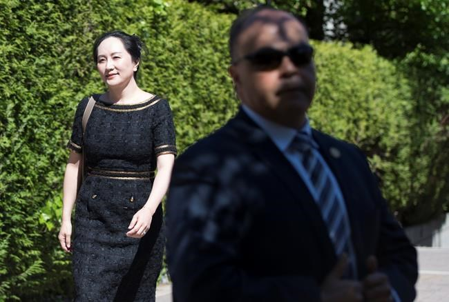 A security guard looks on as Meng Wanzhou, chief financial officer of Huawei, leaves her home to go to B.C. Supreme Court in Vancouver, Wednesday, May 27, 2020. The federal government is trying to block Huawei executive Meng Wanzhou's access to some documents in her extradition case, arguing in court documents that disclosing sensitive information would harm national security. THE CANADIAN PRESS/Jonathan Hayward