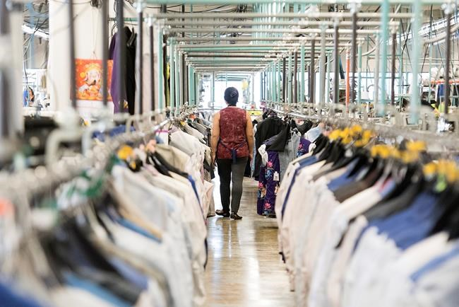 A garment worker walks through a clothing factory in Montreal, Friday, Jan. 31, 2020. The Canadian Centre for Occupational Health and Safety says it is releasing a guide for employers to reopen their businesses amid the COVID-19 pandemic. The online course walks business owners, managers and employees through preparations to return safely to the office, the warehouse and the factory floor. THE CANADIAN PRESS/Graham Hughes